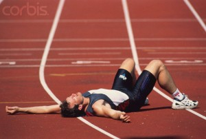 Exhausted runner (male), lying on track